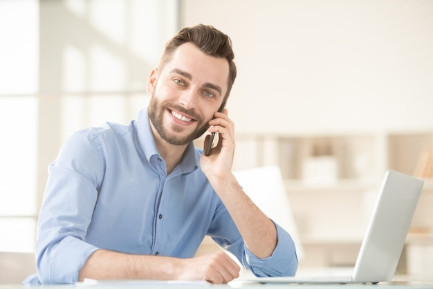 Happy young smiling agent with smartphone consulting one of his clients while sitting in office in front of laptop