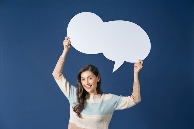 Счастливая молодая улыбающаяся азиатская женщина, держащая и указывая, чтобы скопировать пустые пузыри сообщения