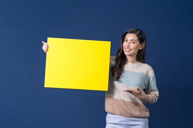 Счастливая молодая улыбающаяся азиатская женщина, держащая и представляющая для копирования пространство пустой желтый