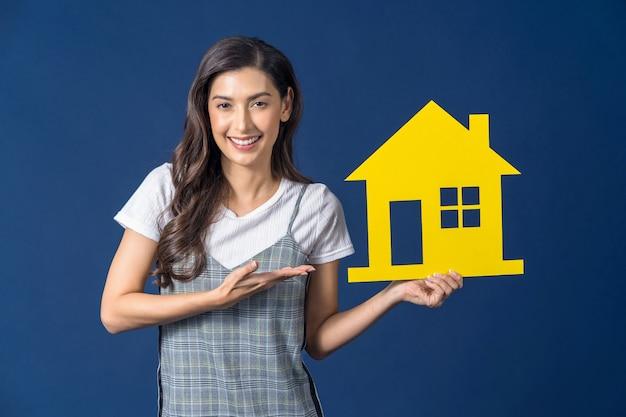Счастливая молодая улыбающаяся азиатская женщина, держащая и представляющая макет дома желтого цвета