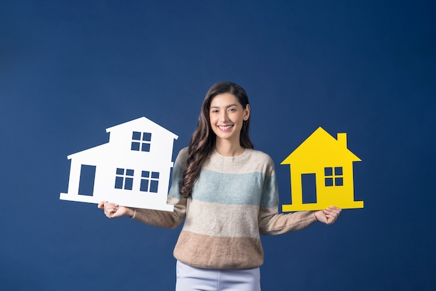 파란색 배경에 두 개의 집 모형 종이를 들고 웃고 있는 행복한 젊은 아시아 여성