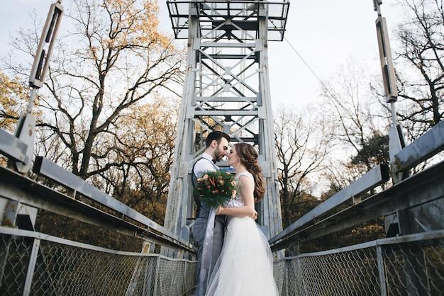 Счастливые молодые улыбающиеся жених и невеста стоят на висячем мосту. свадебные фото в интересном месте