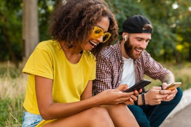 Счастливые молодые улыбающиеся друзья сидят в парке с помощью смартфонов, мужчина и женщина веселятся вместе