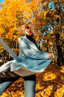 明るい青いコートを着たファッショナブルなサングラスをかけた幸せな若い笑顔の女の子は、黄色い紅葉の公園で動きを歩きます。晴れた日に屋外で面白い女性