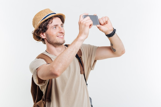 Happy young smiling man with backpack making selfie isolated on a white background