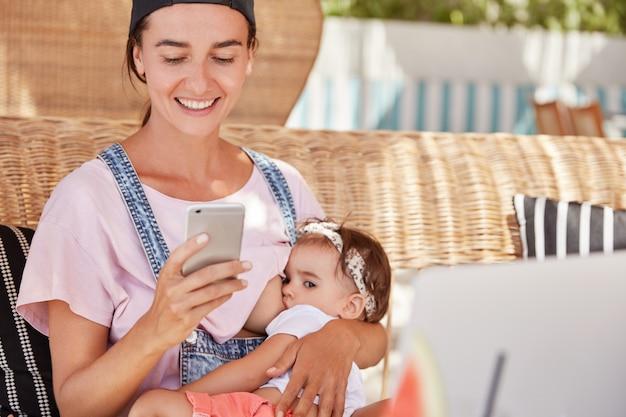 カジュアルな服装で幸せな若い笑顔の母親は、スマートフォンでテキストメッセージを受信して喜んでいる彼女の小さな赤ちゃんを授乳し、彼女の子供を愛し、オンラインショッピングをしています。母性と出産のコンセプト