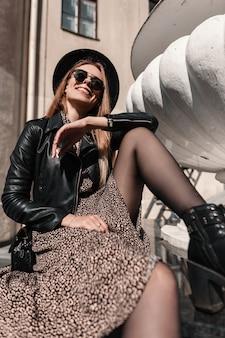Счастливая молодая улыбающаяся женщина в модной одежде с винтажным платьем и черной кожаной курткой с сумочкой сидит на улице