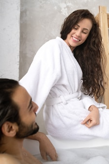 Счастливая молодая улыбающаяся женщина в белом халате разговаривает со своим мужем, сидя перед ним в ванной