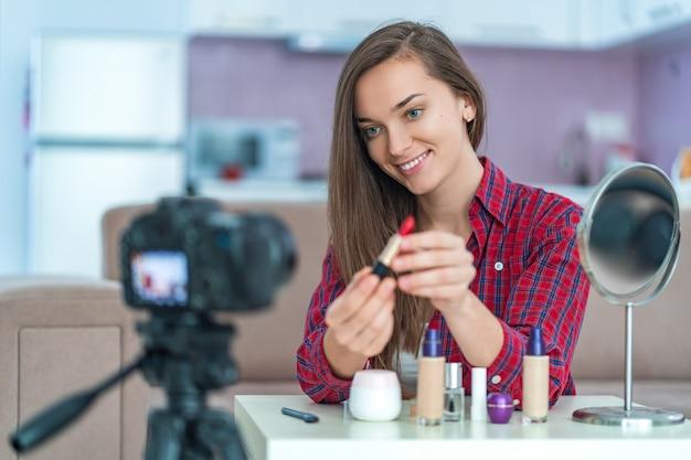 幸せな若い笑顔の女性のビデオブロガーが保持し、ライブストリーミング中に聴衆に赤い口紅を示し、自宅で化粧や化粧品についての彼女の美容ブログを記録します。ブログ