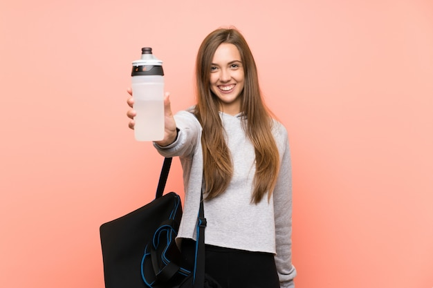 Happy young sport woman over isolated pink  with a bottle of water