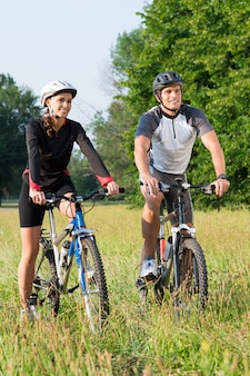 Happy young sportive man and woman on bicycle