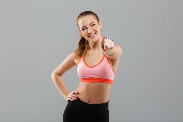 あなたを指している幸せな若いスポーツ女性。