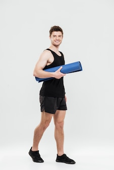 Happy young sportsman holding fitness rug