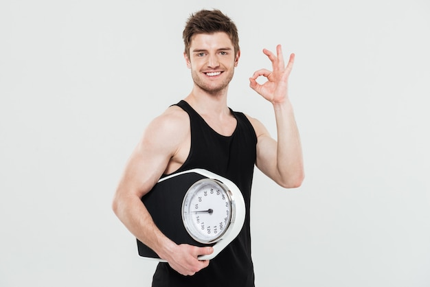 Happy young sportsman holding scales showing okay gesture