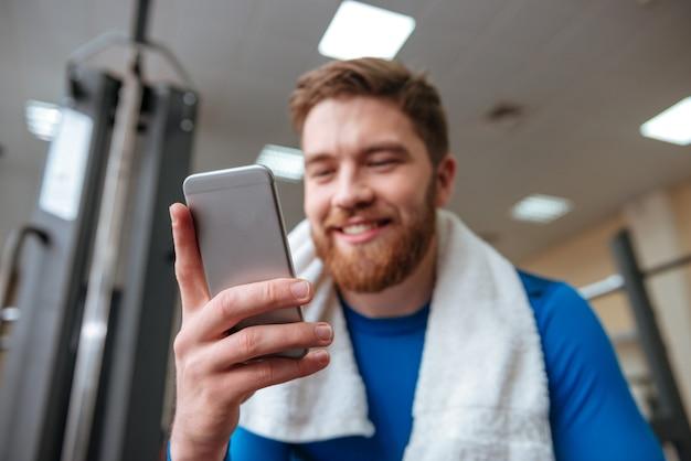 電話を見てジムで幸せな若いスポーツマン。