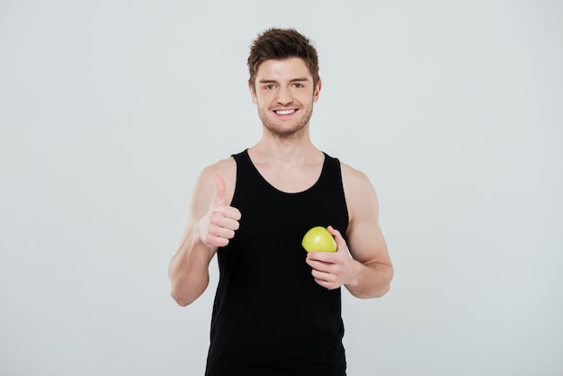 Happy young sportsman standing isolated over white background