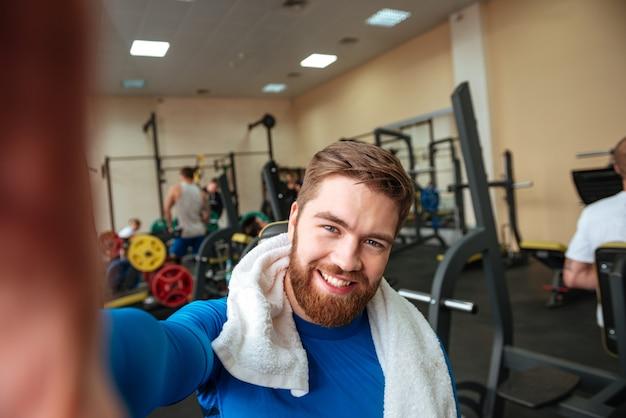 タオルで幸せな若いスポーツマンは、selfieを作ります。