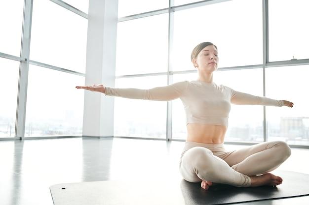 Счастливая молодая спортсменка в спортивной одежде сидит с вытянутыми руками и скрещенными ногами на коврике во время расслабляющих упражнений йоги