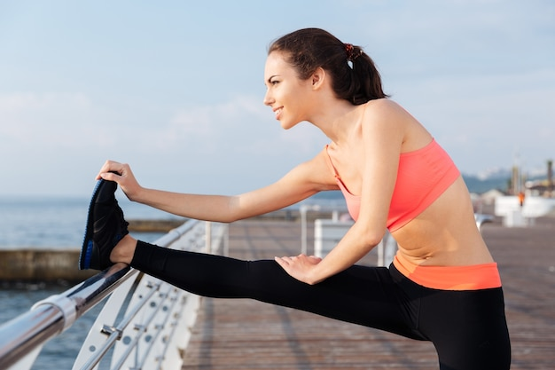 Happy young sportswoman standing and stretching legs on pier