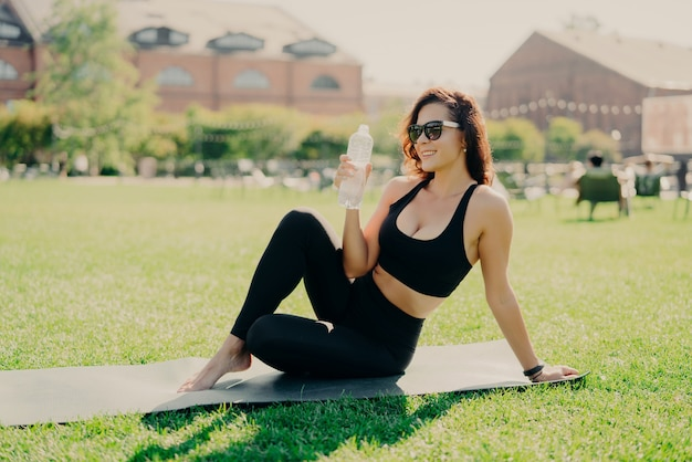 Happy young sporty european woman has rest after training poses on fitness mat with bare feet drinks water dressed in activewear sunglasses leads healthy lifestyle. people workout hydration concept