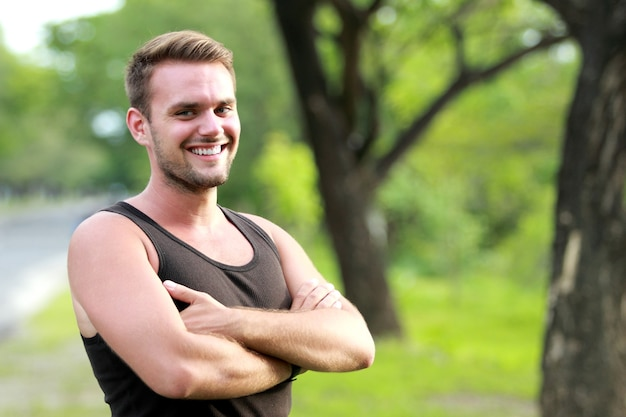 Happy young sporty man smiling and pose with folded arm Premium Photo