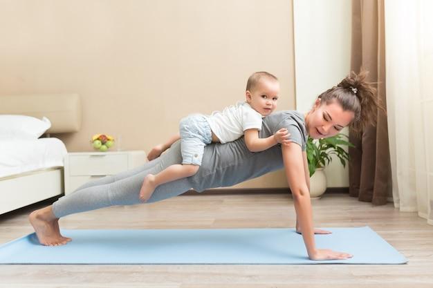 육체적인 요가나 필라테스 운동을 하는 행복한 젊은 스포티 임산부