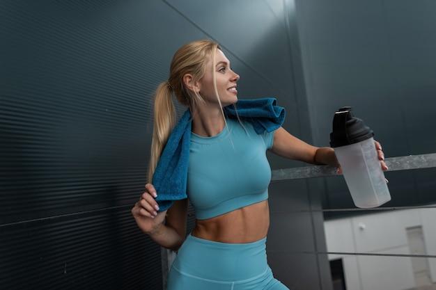 파란색 스포츠웨어 훈련을 받고 물 한 병과 수건을 들고 도시에서 즐기는 행복한 젊은 스포티 여성