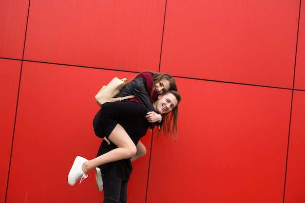 Happy young state of paraná the red background of the wall, the girl jumps on guy