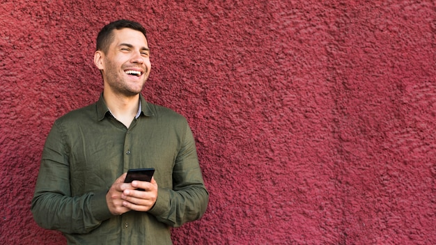 Happy young stubble man holding cellphone standing near rough wall