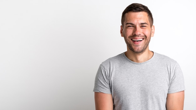 Happy young stubble man laughing and standing over white backdrop
