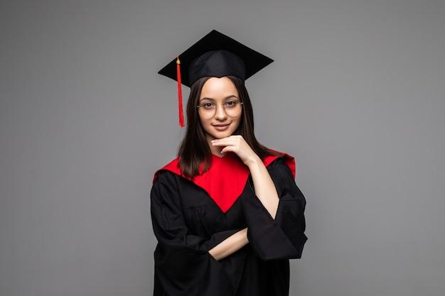 Felice giovane studente con diploma su grigio