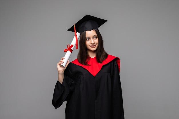 Счастливый молодой студент с дипломом на сером