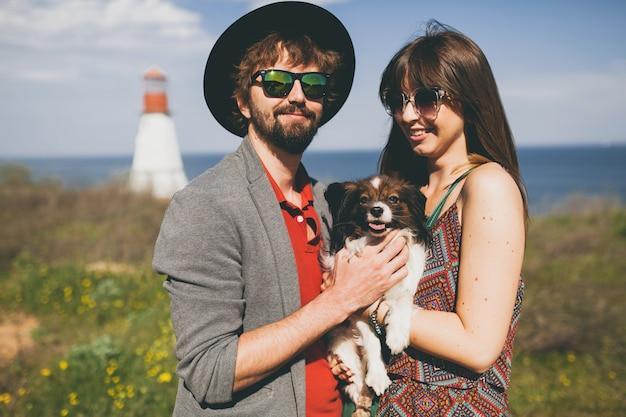 Счастливая молодая стильная хипстерская пара в любви гуляет с собакой в сельской местности