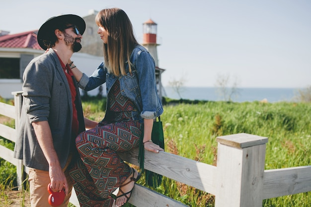 Happy young stylish hipster couple in love walking in countryside, summer style boho fashion