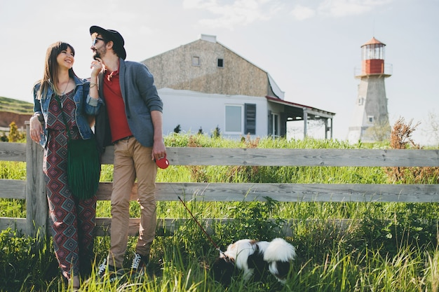 Happy young stylish hipster couple in love walking with dog in countryside, summer style boho fashion