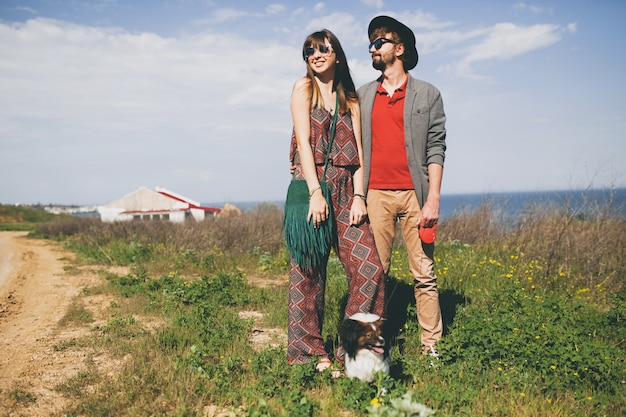 Happy young stylish hipster couple in love walking with dog in countryside
