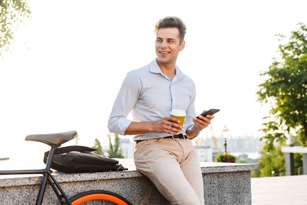 Счастливый молодой стильный мужчина держит мобильный телефон