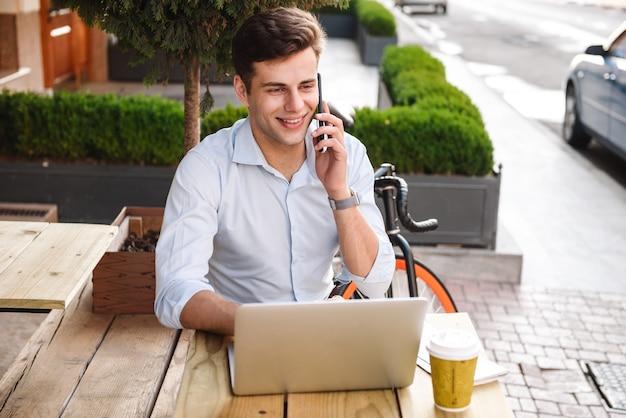 携帯電話で話しているシャツの幸せな若いスタイリッシュな男