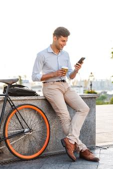 Счастливый молодой стильный человек с помощью мобильного телефона