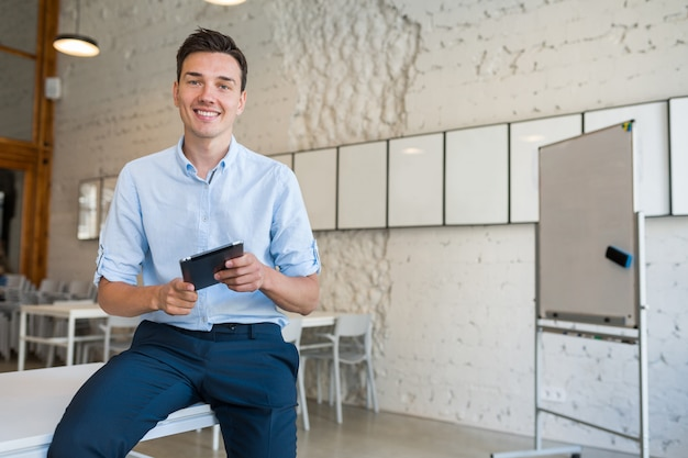 Happy young stylish smiling man in co-working office, startup freelancer holding using tablet,