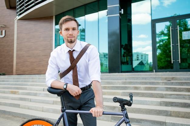 Счастливый молодой успешный бизнесмен, глядя на вас, опираясь на свой велосипед