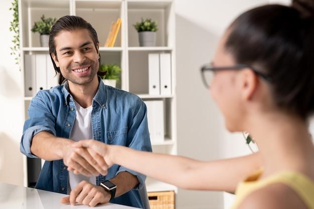 Счастливый молодой успешный бизнесмен, пожимая руку новому деловому партнеру после заключения сделки, глядя на нее с улыбкой