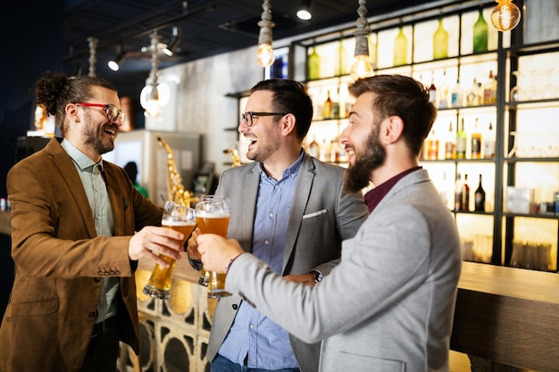 Happy young successful businessmen drinking beer and talking at pub after work