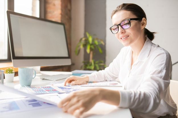 Happy young successful businesswoman sitting by desk with lots of papers in front and reading one of them at work