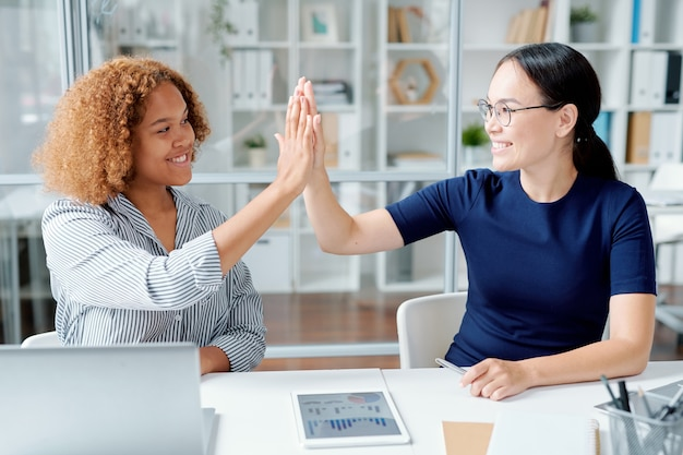 Happy young successful colleagues giving high five to one another over desk after finishing up with data analysis