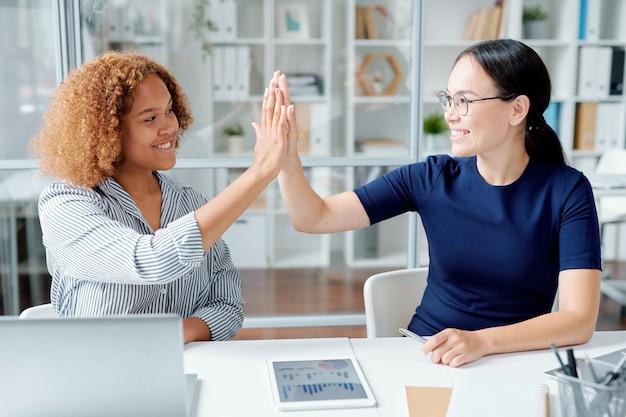 Счастливые молодые успешные коллеги дают пять друг другу за столом после завершения анализа данных