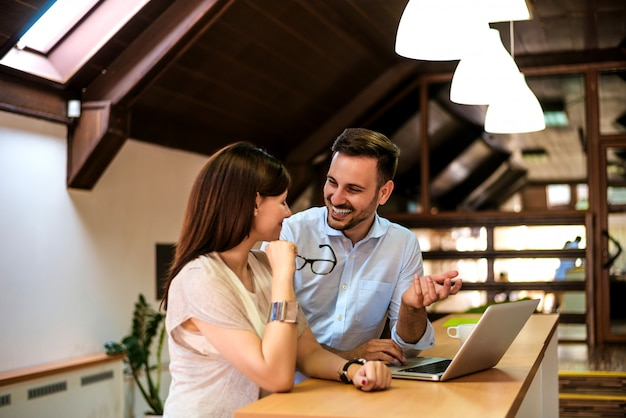 Happy young successful couple at home with laptop