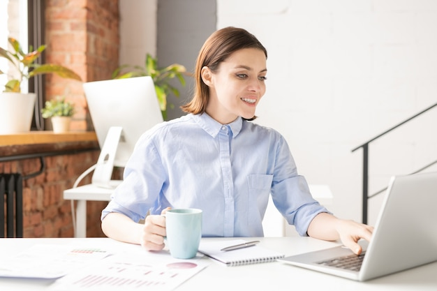 Happy young successful female broker in shirt looking at laptop display while surfing in the net during coffee break in office