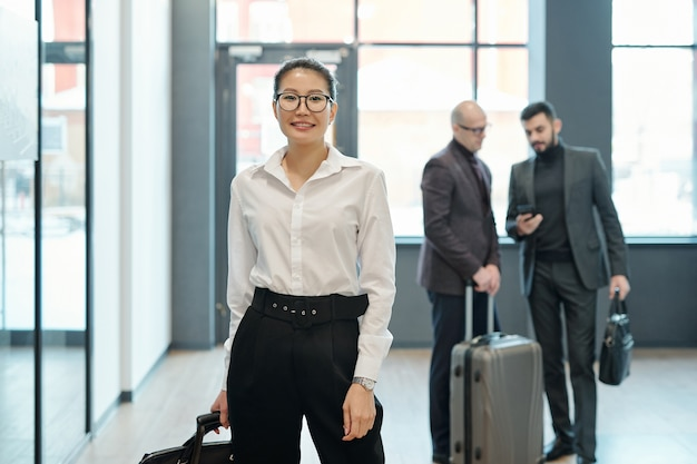 Happy young successful female business traveler with luggage