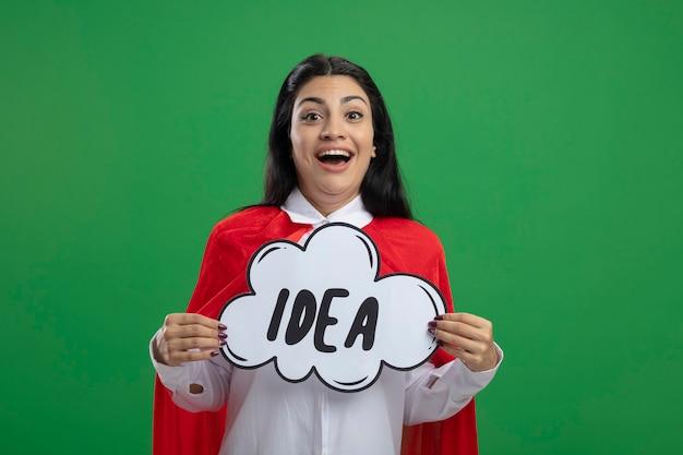아이디어 거품과 조롱을 들고 행복 한 젊은 슈퍼 우먼 녹색 벽에 고립 된 앞에서보고 웃 고